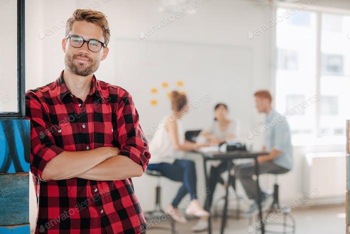 Entspannter Geschäftsmann im Büro mit Kollegen im Hintergrund