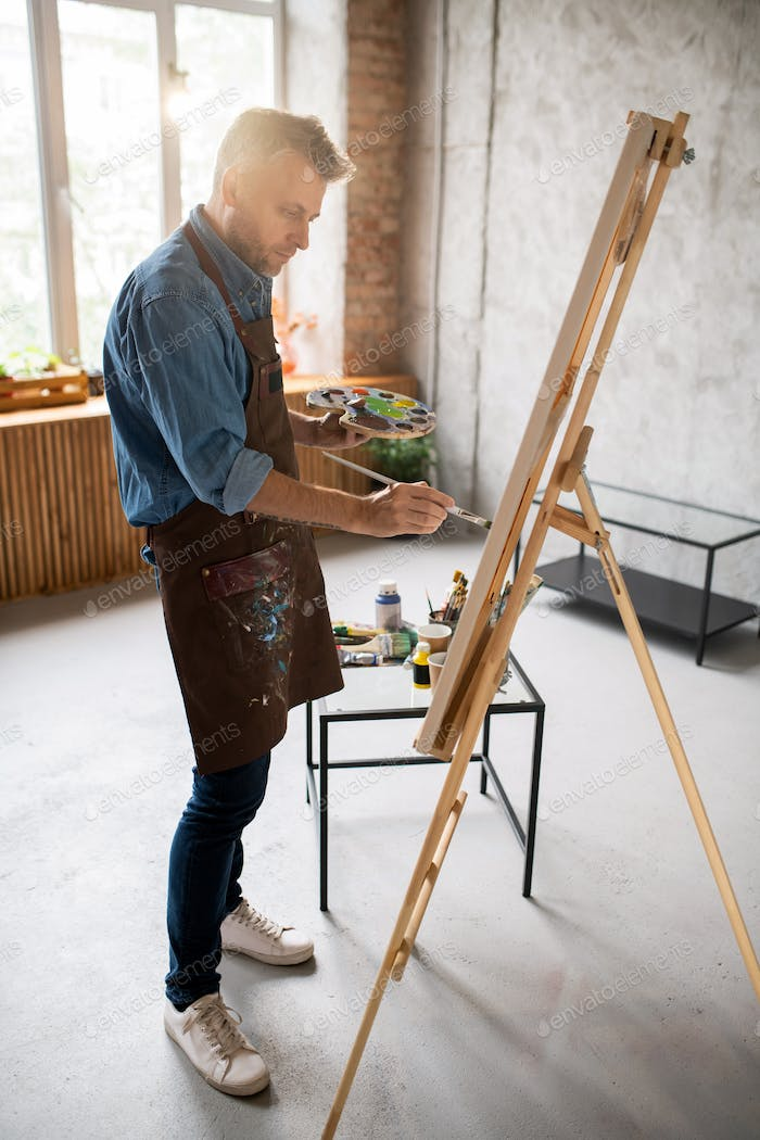 Casual man in apron standing in front of easel and painting with water colors