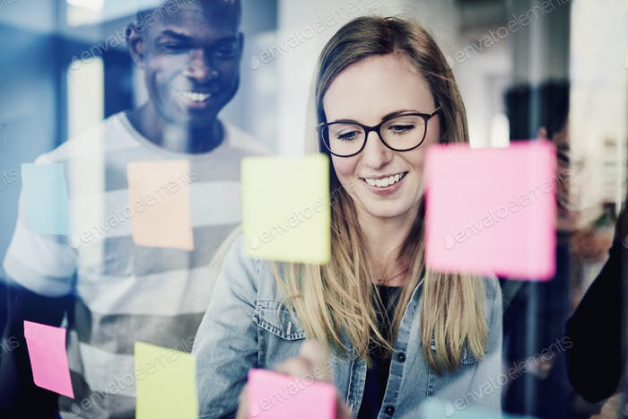 Diverse businesspeople brainstorming with sticky notes on a glass wall