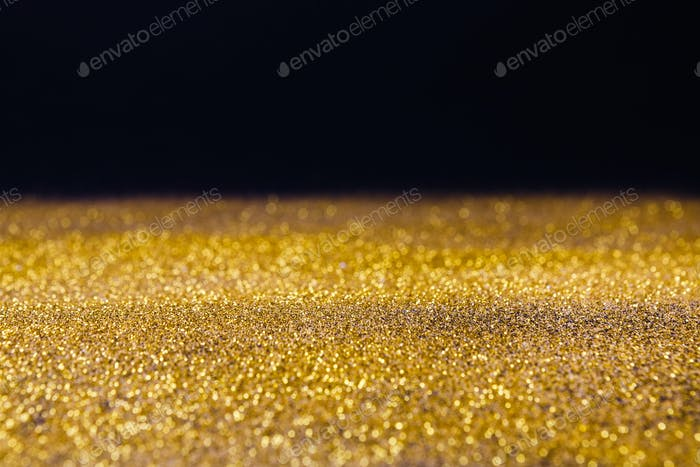 Golden glitter sand rain texture on black, abstract background.