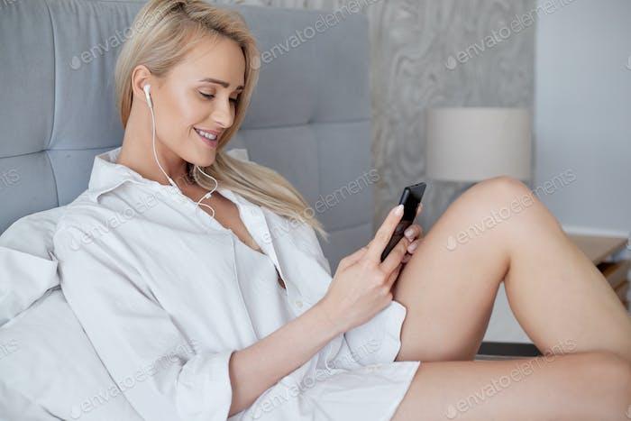 Entspannte, lächelnde blonde Frau im weißen Bett liegend und mit einem Smartphone