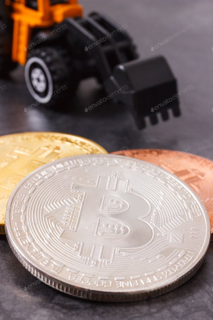 Bitcoins and miniature excavator, symbol of new virtual money and mining cryptocurrency