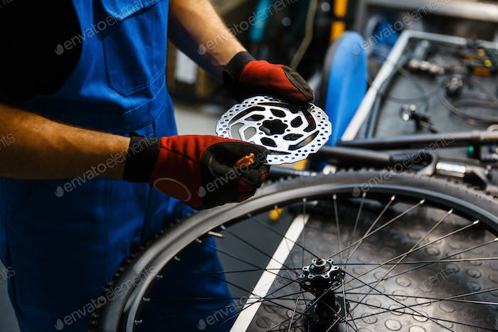 Bicycle repair in workshop, man fixing brake disk