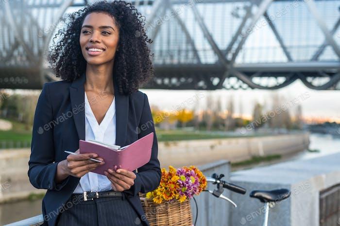 Business schwarze Frau mit Vintage-Fahrrad am Fluss suchen ein
