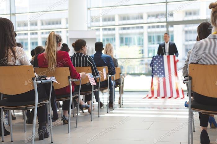 Geschäftsmann spricht auf einem Business-Seminar im Bürogebäude mit amerikanischer Flagge