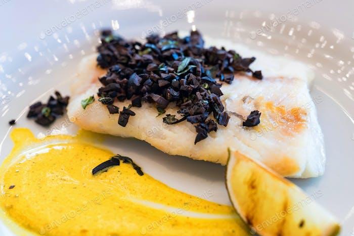 Zander Filet mit Gemüse und Oliven auf weißem Teller