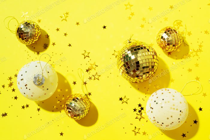 Christmas white and gold decorations, mirror disco balls, star sparkles over yellow background. Flat
