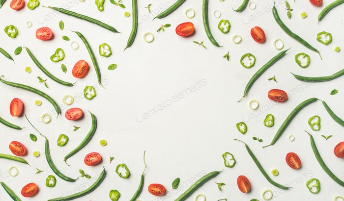 Flat-lay of vegetable slices over white wooden background, copy space