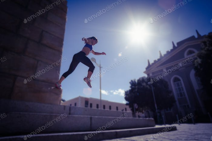 Athletic woman jumping off the stairs in the city