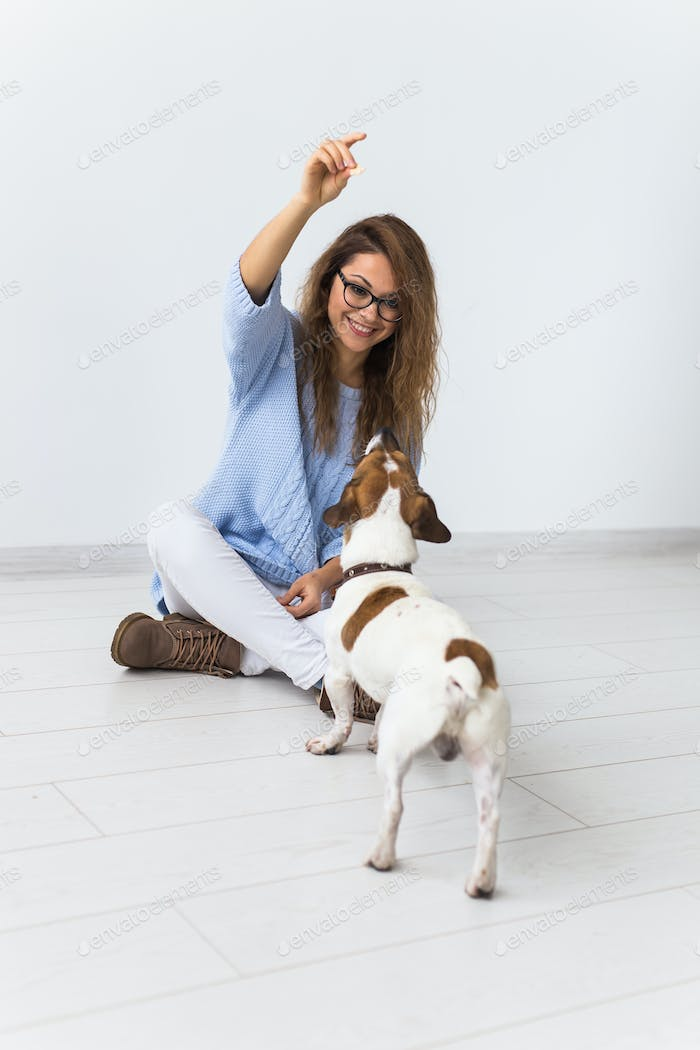 Cheerful female in blue sweater playing with her favourite pet.