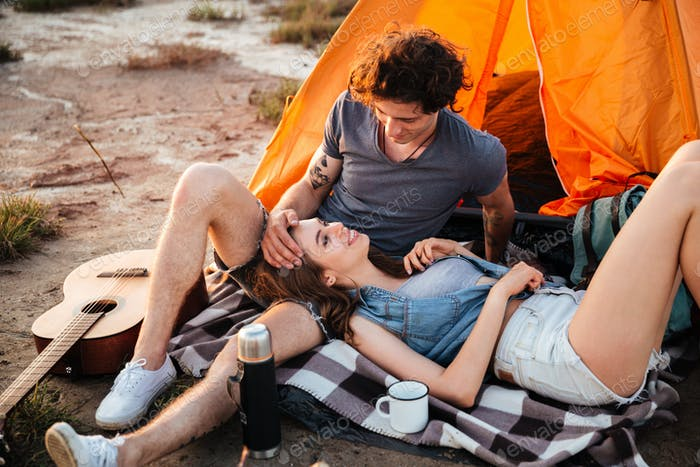 Portrait of cheerful couple relaxing at the camp tent