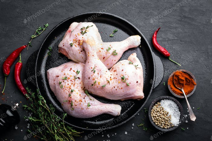 Raw chicken quarters, legs in a pan on a dark background. Top view.