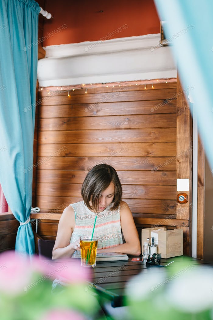 Girl in cafe with drink and tablet