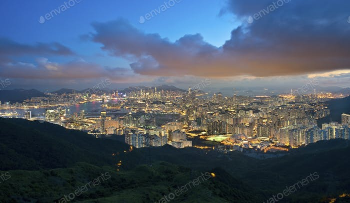 View across Kowloon with city of Hong Kong with illuminated skyscrapers at dusk.