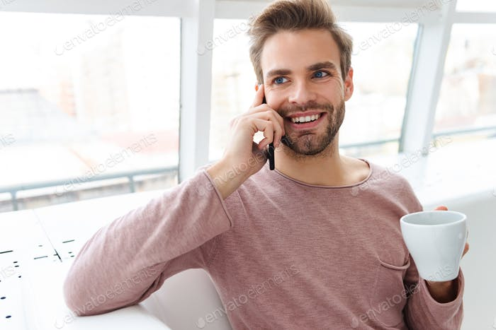 Image of young bearded man talking on smartphone in cafe indoors