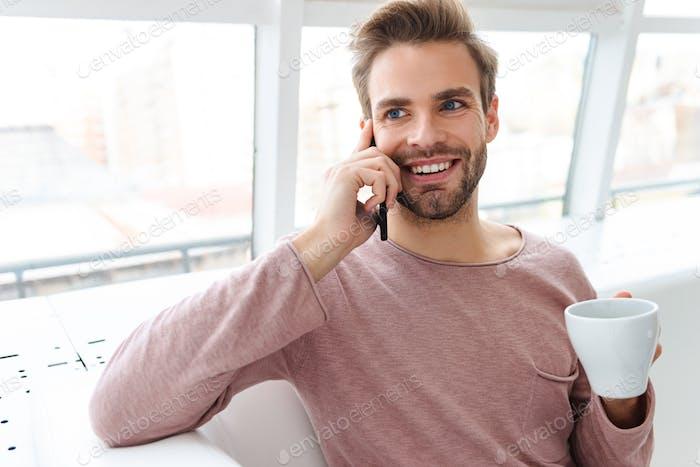 Bild des jungen bärtigen Mannes im Gespräch auf Smartphone im Café drinnen