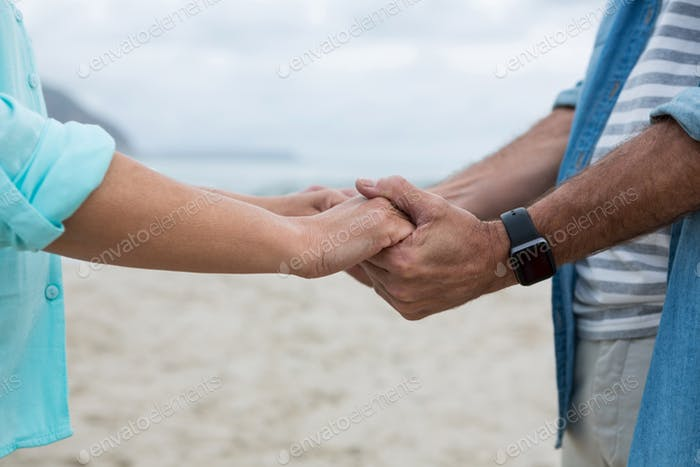 Mid section of couple holding hands on beach