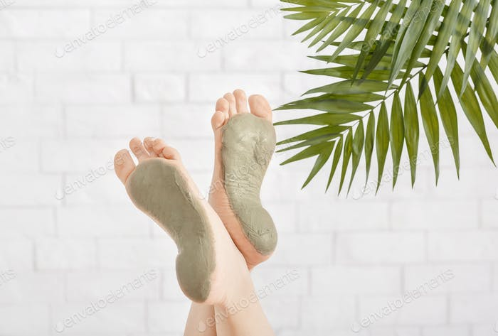 Beauty care in spa. Foot care with clay on white brick wall
