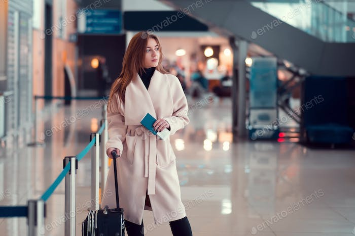 Young girl with a suitcase in the airport.