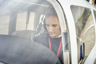 Front view from outside of a female pilot in the cockpit of an airplane.
