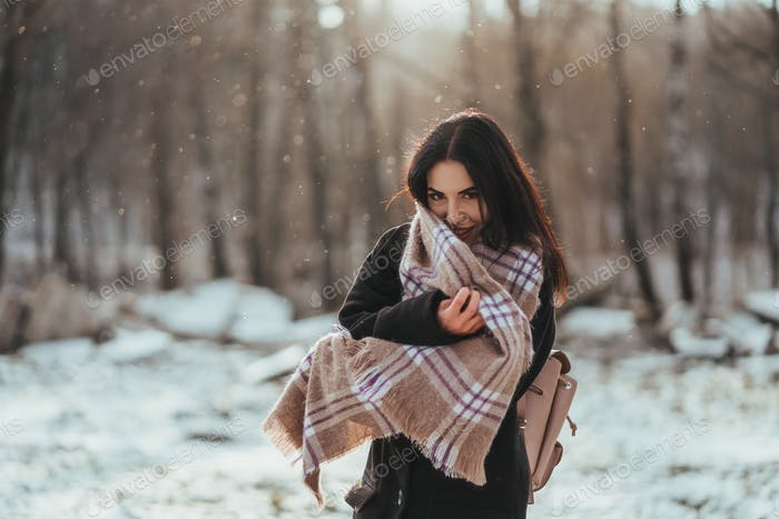 Young beautiful model posing in winter forest. stylish fashion portrait