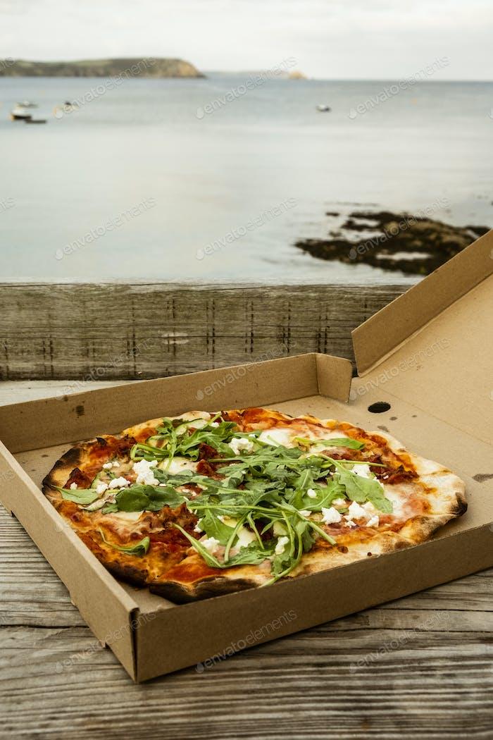 A takeaway pizza in a brown box.