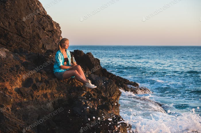 Young blond woman tourist sitting on rocks