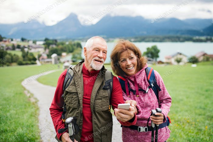 Senior pensioner couple with hiking in nature, using smartphone.