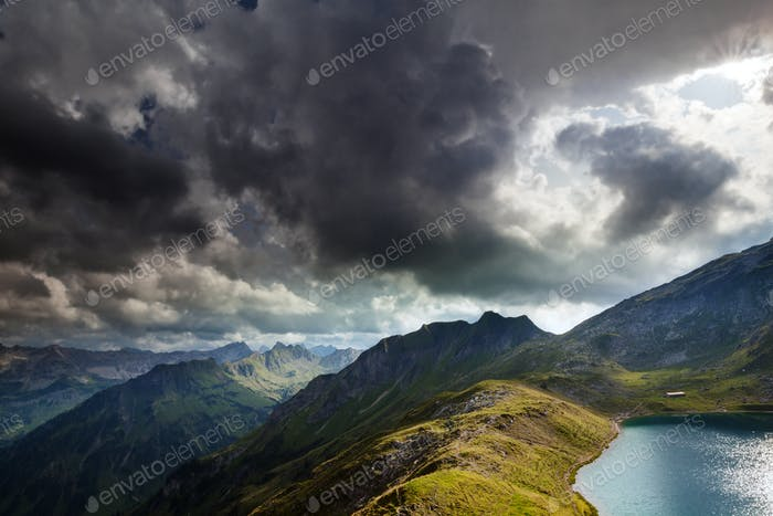dramatic sky over alpine lake in mountains
