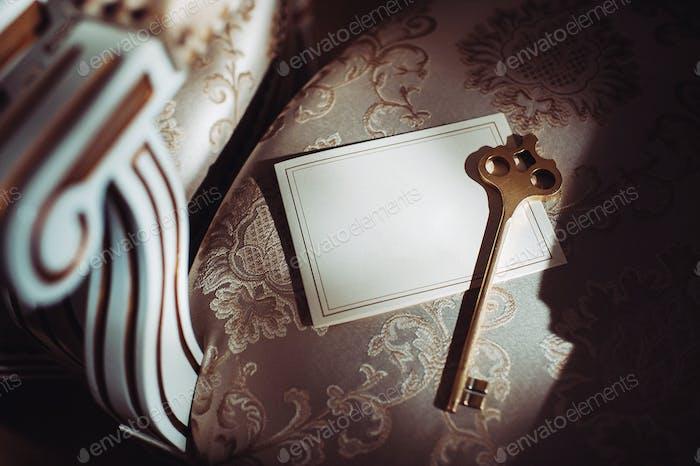 eine Postkarte und ein alter Schlüssel auf dem Hintergrund eines alten natürlichen Stuhls. Leerer Platz für eine Postkarte mit