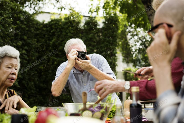 Senior man taking photo of friends with retro film camera