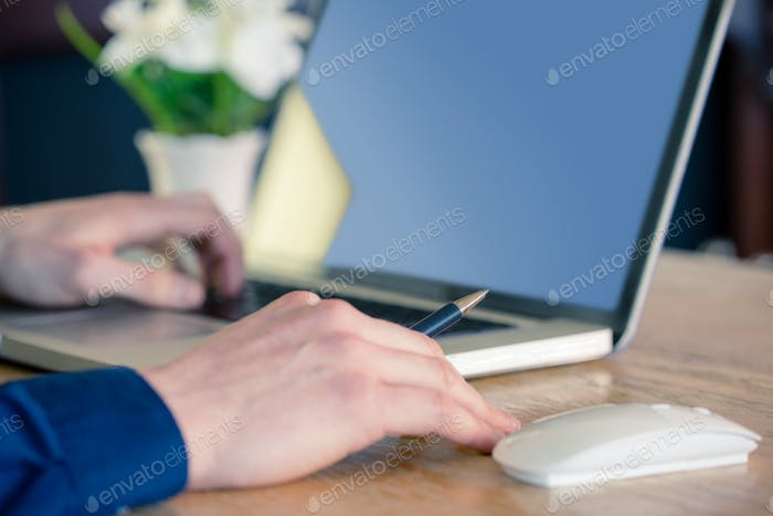 Close up of businessman working at desk in his office
