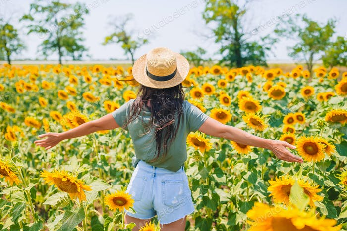 Young woman enjoying nature on the field of sunflowers