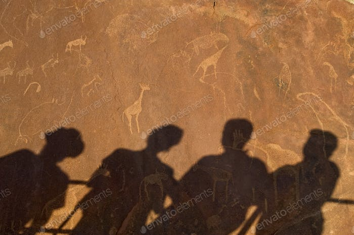 The shadows of tourists on a flat rock at  Twyfelfontein World Heritage rock art site