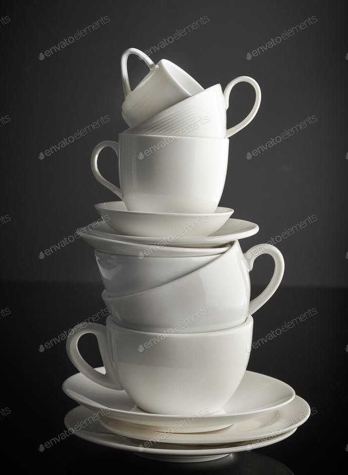 stack of white coffee cups and plates