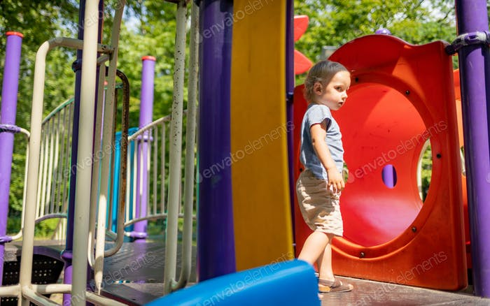 Little child boy playing on playground in the city park