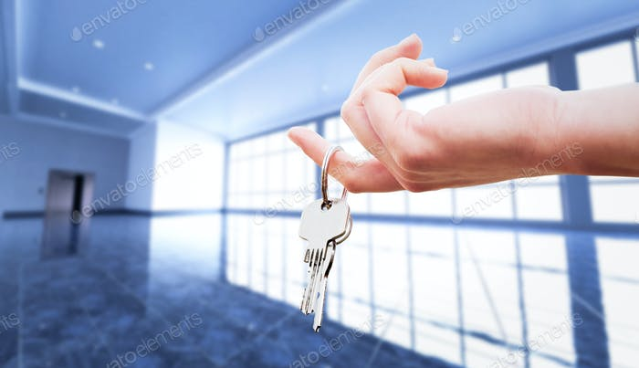 Woman's hand holding the keys to an apartment.