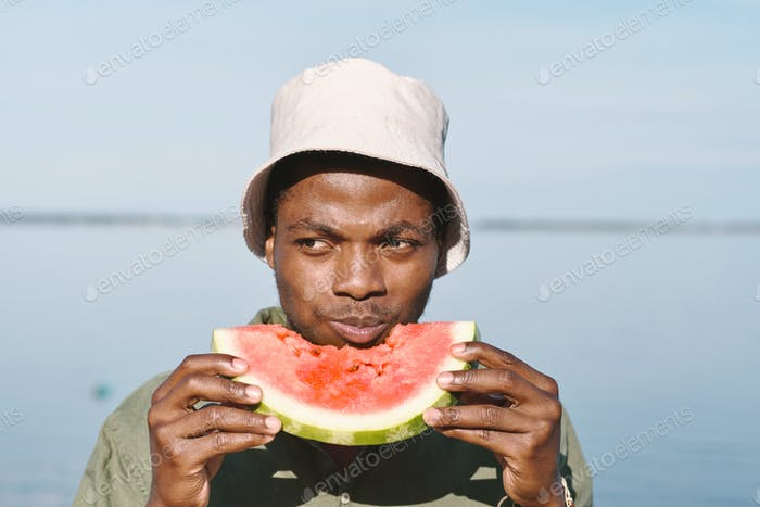 Young African man biting and eating fresh watermelon