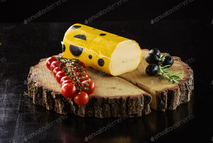 Piece of Salami cheese, cherry tomatoes and olives on wooden boa