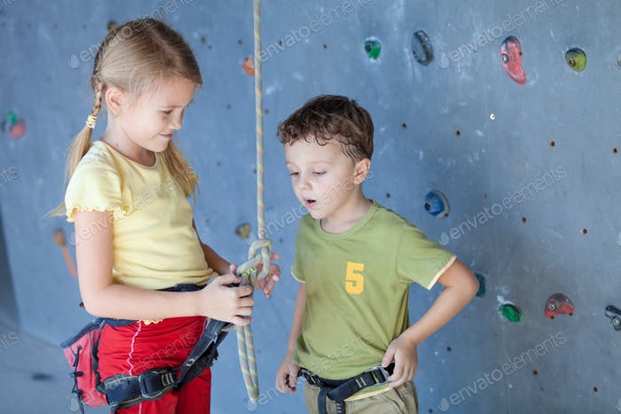 brother and sister standing near a rock wall for climbing