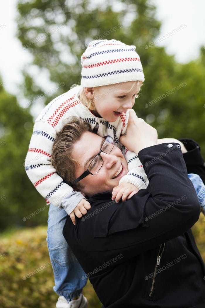 Cheerful father carrying son on shoulders at park