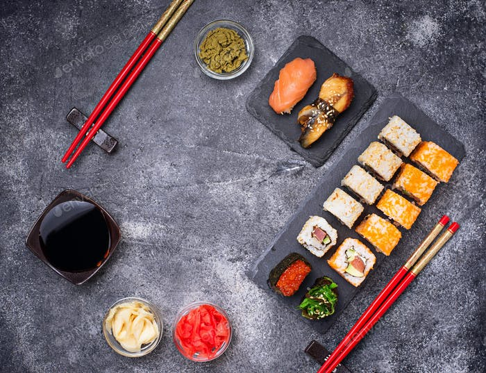 Sushi and roll set on black table