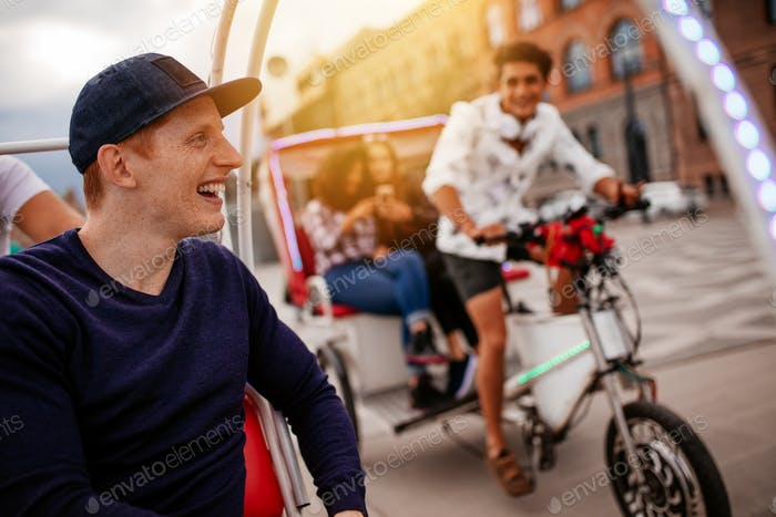 Happy young man enjoying tricycle ride with friends