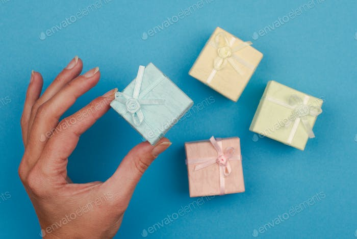 hand holding a small gift box on blue background