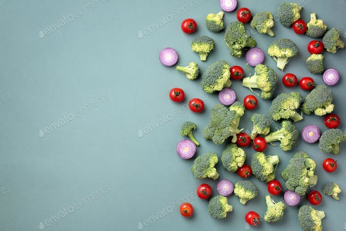 Creative layout of broccoli, tomatoes, onion on green paper background. Top view. Food pattern in