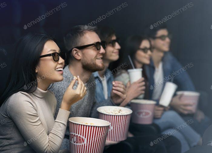 Happy people in 3D glasses watching movie in dark cinema
