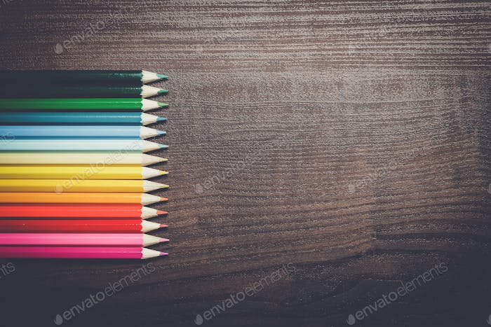 multicolored pencils over brown table background