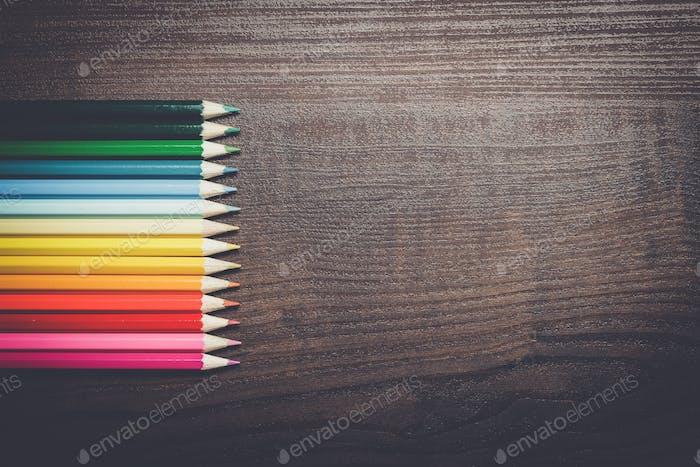 Buntstifte über braunem Tischhintergrund