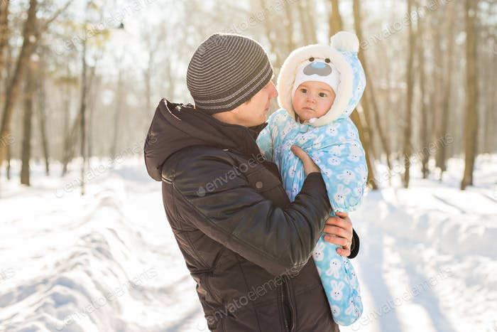 Happy family on a winter walk in nature. Dad with baby boy