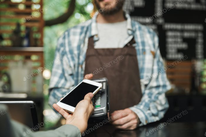 Portrait of caucasian barista man holding consumer terminal for
